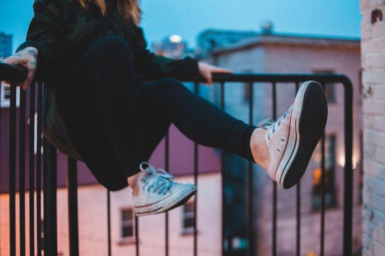Frau in weißen Sneakern auf Balkon}