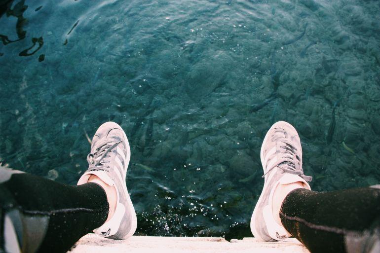 Blick hinab auf über Gewässer baumelnde Füße in Adidas Sneakern