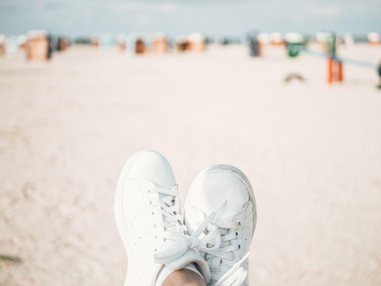 Blick auf Füße in weißen Sneakern an Strand}
