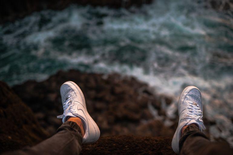 Blick hinab auf weiße Nike Sneaker über Meer}