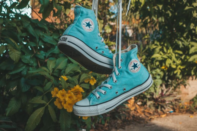 Hellblaue Converse All Stars baumeln an Schnürsenkeln}