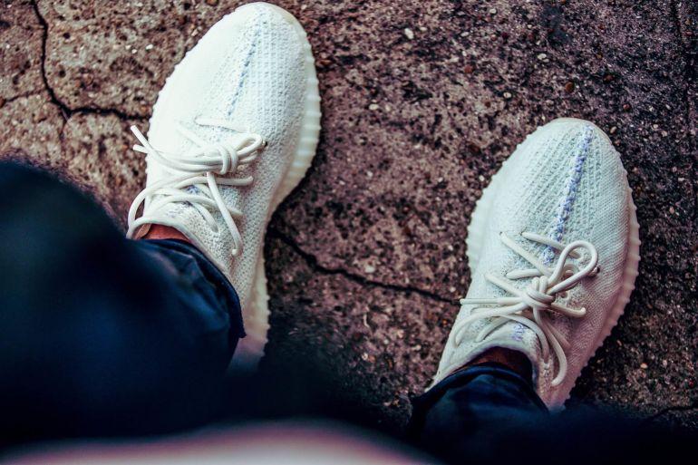Blick hinab auf Füße in weißen Sneakern auf Asphalt}