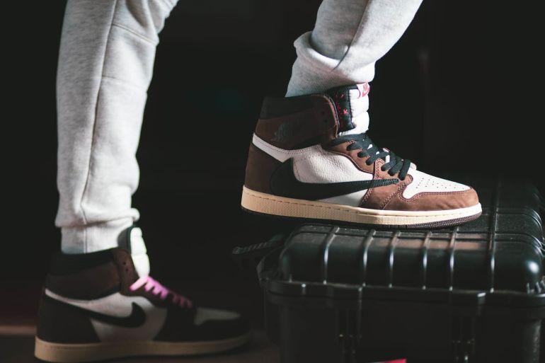 Mann in grauen Sweatpants stellt Fuß in braun-weißem Nike Sneaker auf Koffer}