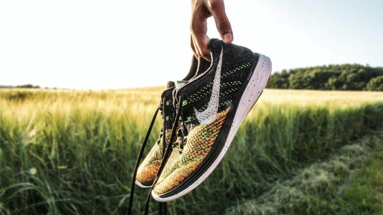 Hand hält bunte Nike Sneaker vor Weiden}