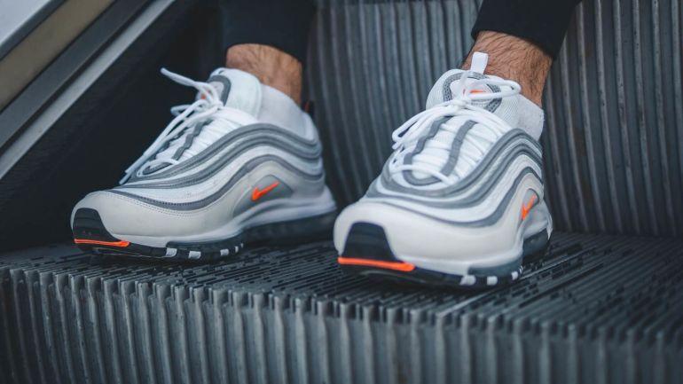 Mann in weißen Nike Sneakern auf Rolltreppe