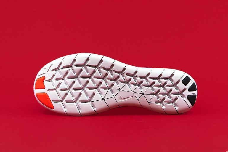 Sole eines Nike Sneaker vor rotem Hintergrund