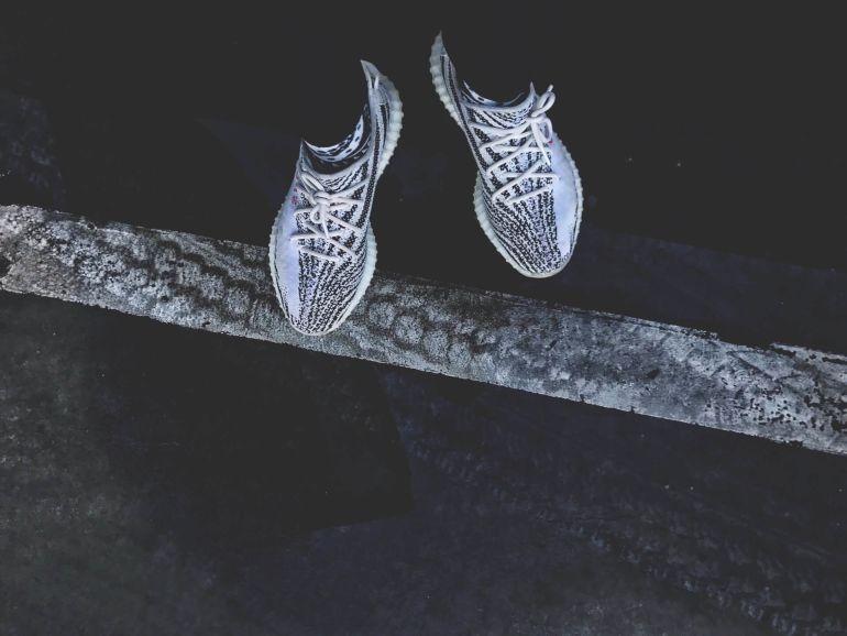 Blick auf Füße in schwarz-weißen Yeezys
