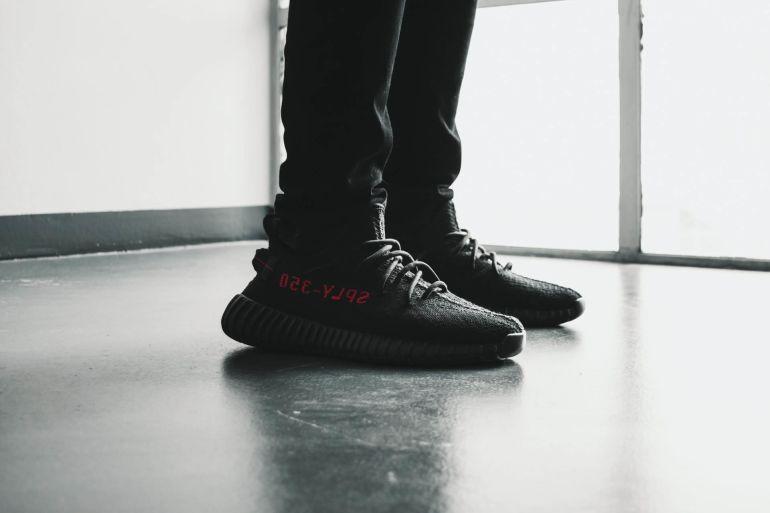 Füße in schwarzen Yeezys mit rotem Code Print