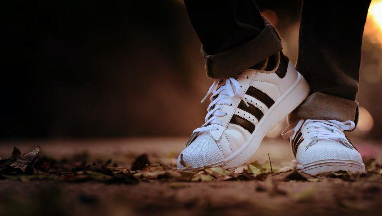 Füße in schwarz-weißen Adidas Sneakern