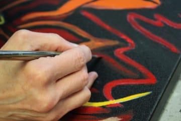 Hombre pintando sobre lienzo negro