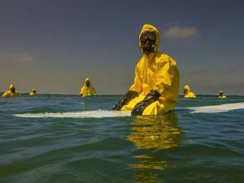 Young man sitting on a surfboard in the water wearing a hazerdous materials suit.
