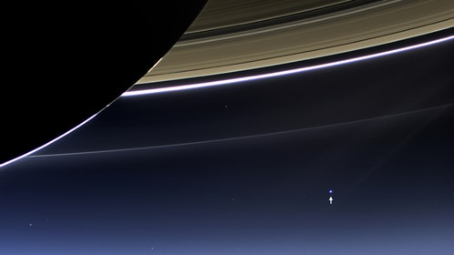 Quarter of Saturn with rings. The small dot at the end of the arrow (lower right quarter) is Earth.
