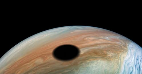 Image of Jupiter surface with large round black shadow made by an eclips of one of her moons.