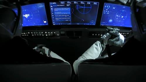 Astronaut in pressure suit in front of spacecraft flat panel controls.