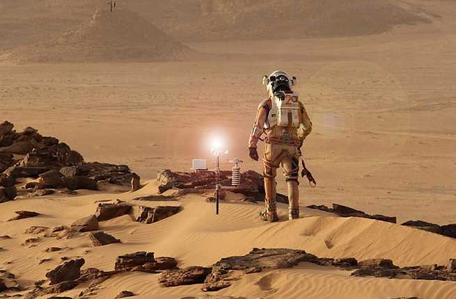 Image of single pressure suited person on a Mars hilltop looking down on a small compound.