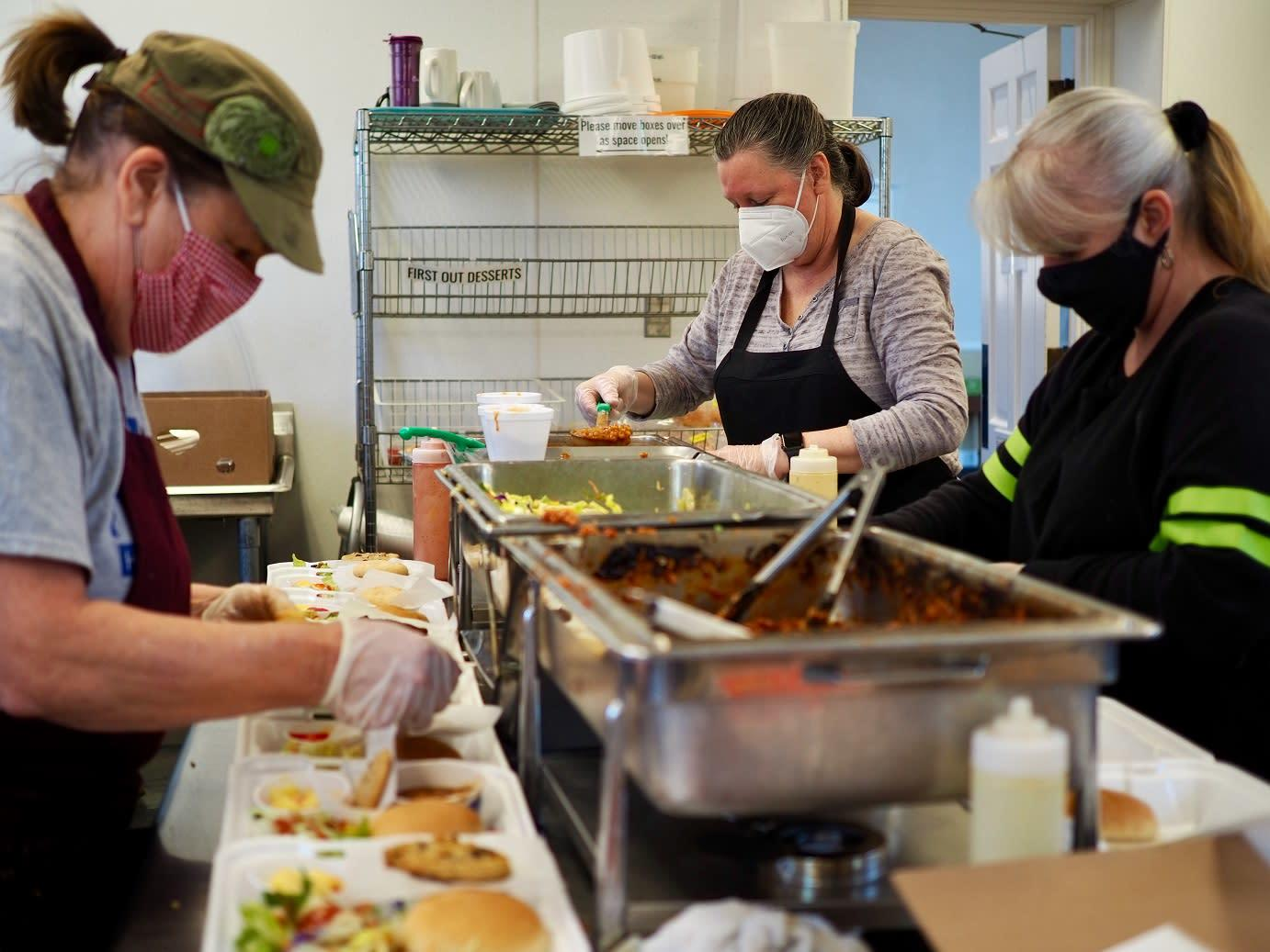 Photo of 3 volunteers and staff members at the Community Kitchen putting together to-go meals.
