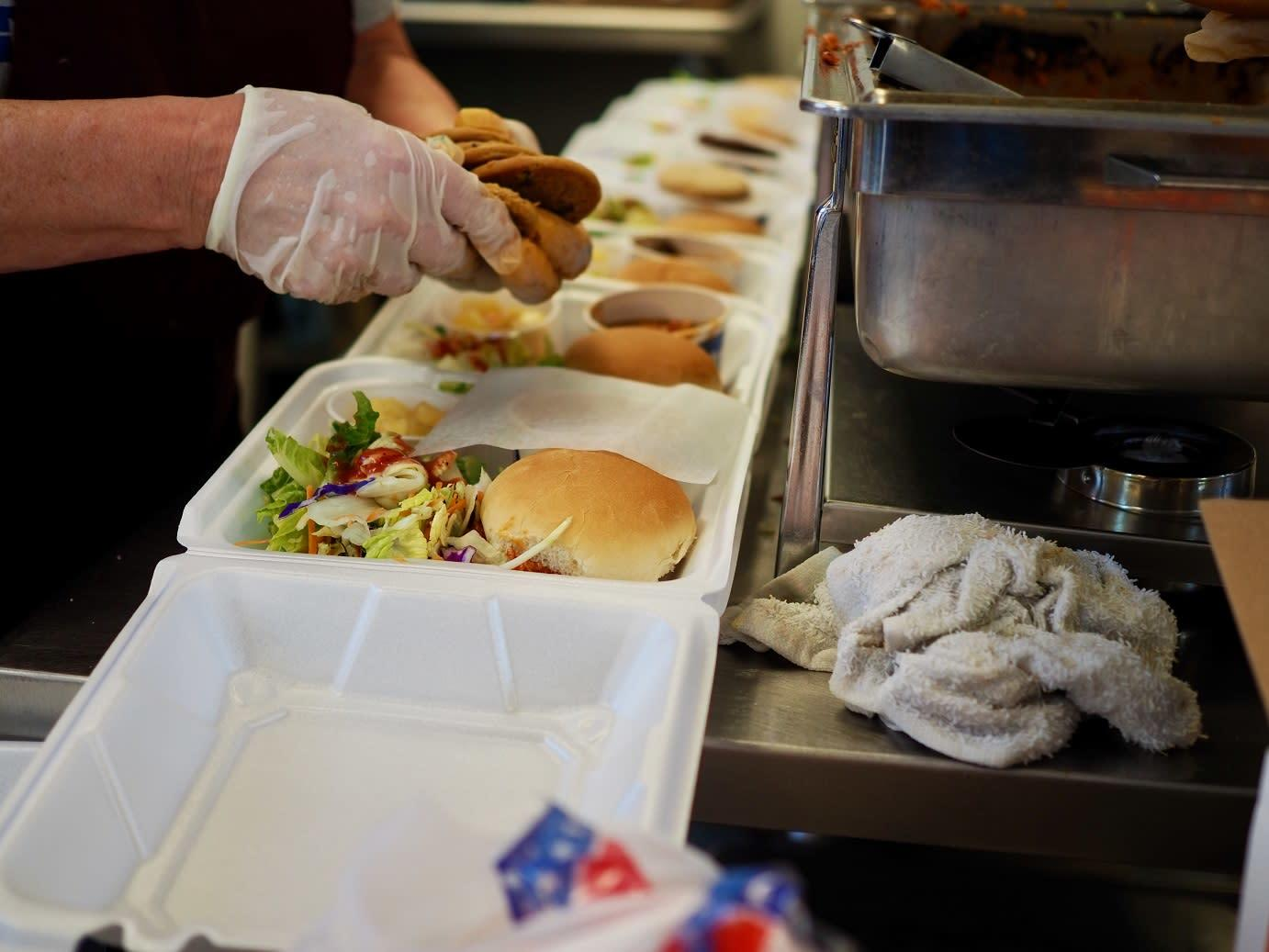 Close-up image of a volunteer assembling to-go meals: pulled pork sandwiches with salad, fruit, and a cookie.
