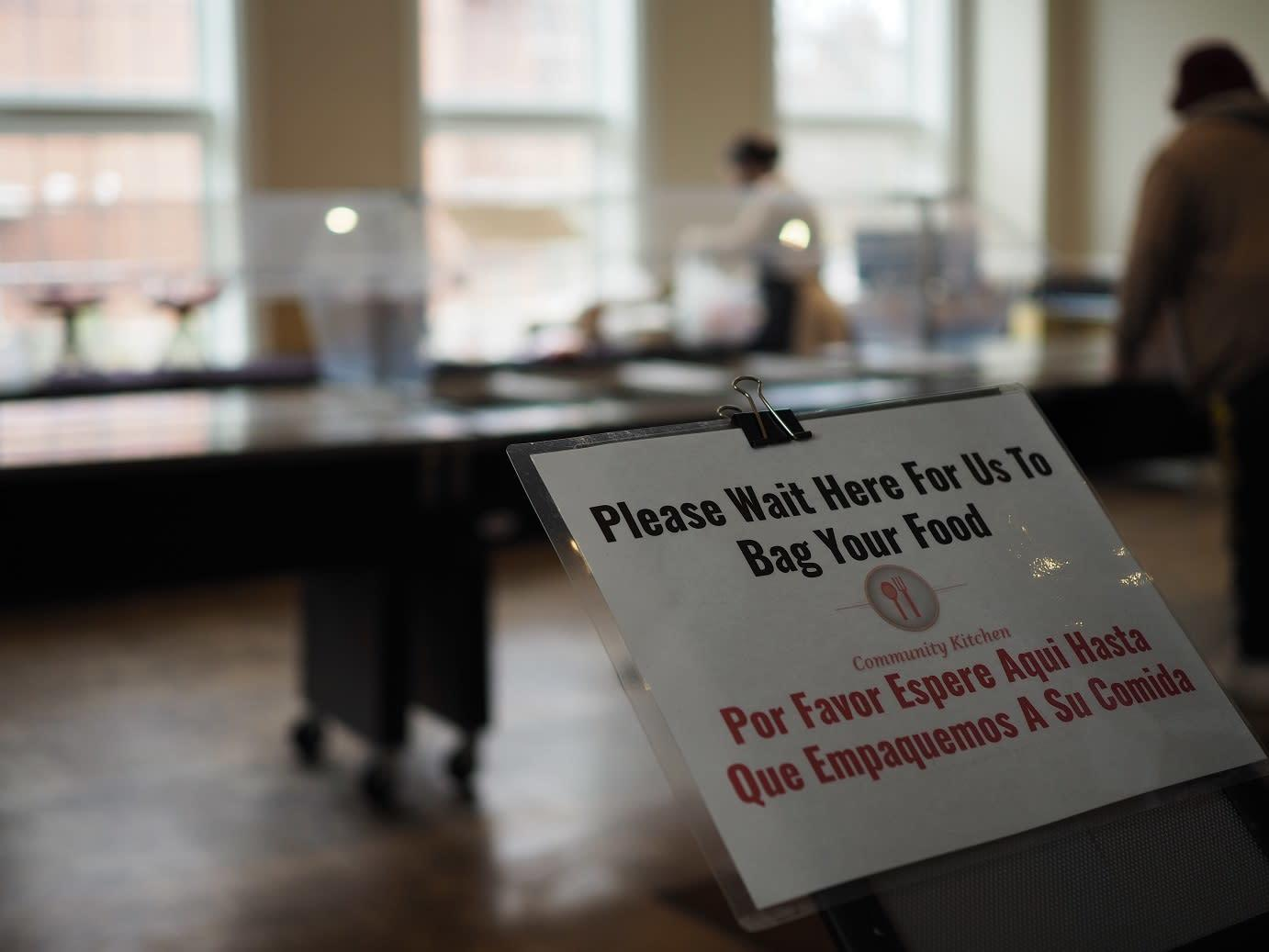 Image of a sign letting guests know to wait their turn for their food to be bagged up to-go