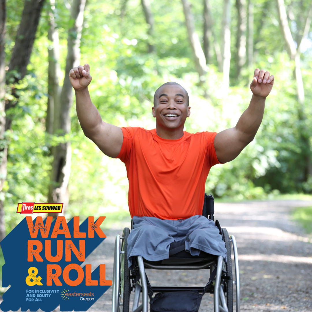 Man in wheelchair, wearing an orange shirt and gray shorts. He has his arms up in the air to celebrate, smiling.