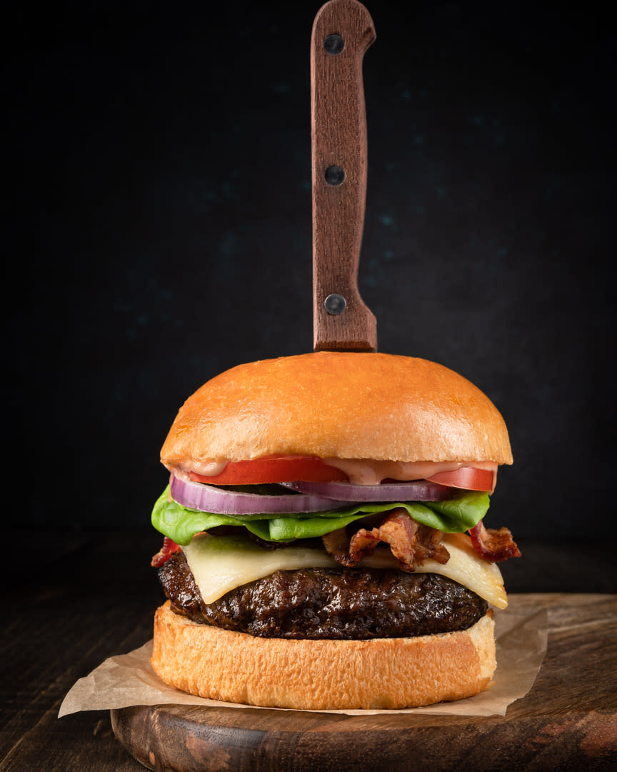Food photography of a burger with meat, cheese, bacon, lettuce, tomato, sauce