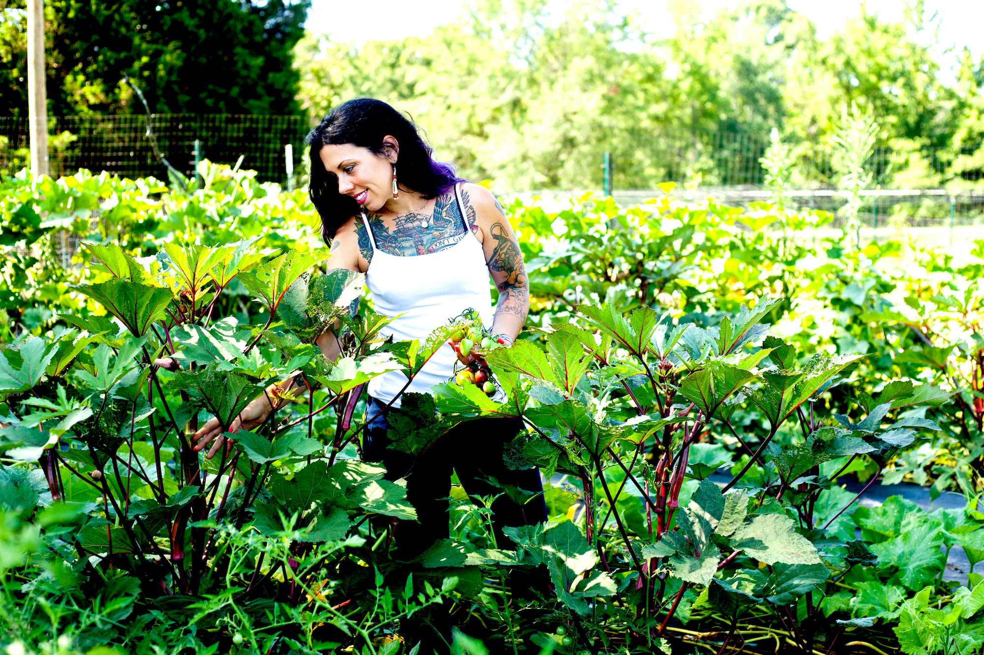 Founder of Virginia Free Farm, Amyrose Foll, stands in a garden thick with tall plants that have large green leaves.