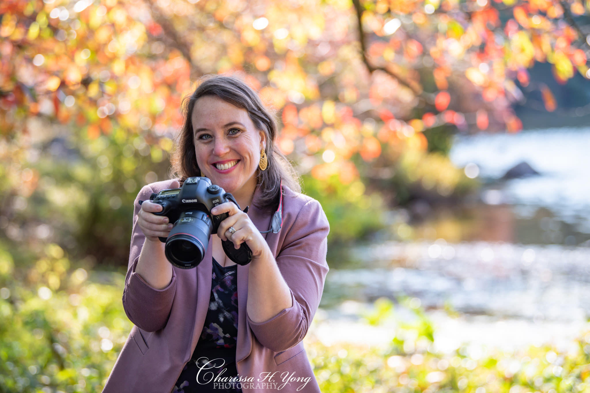 A woman holding a DSLR camera at a park during Fall season.