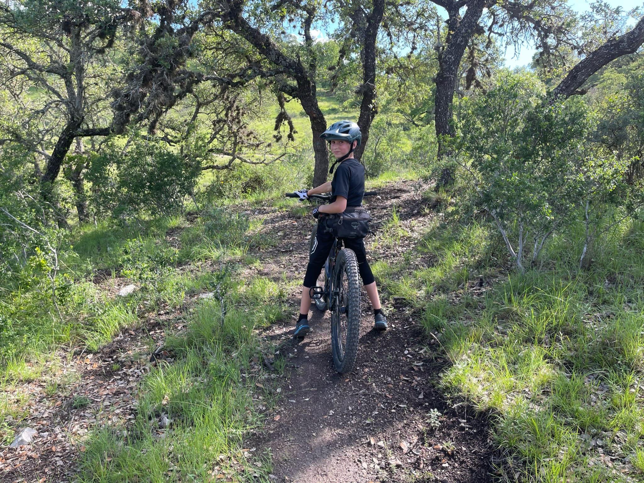 boy on bike in woods