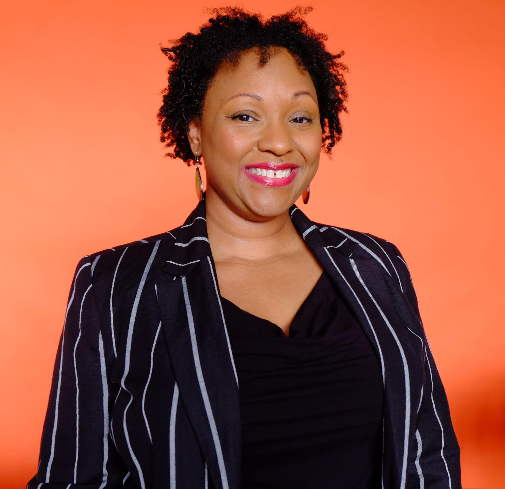 Joyous black female in a black shirt with a black and white striped blazer smiling in front of an orange background