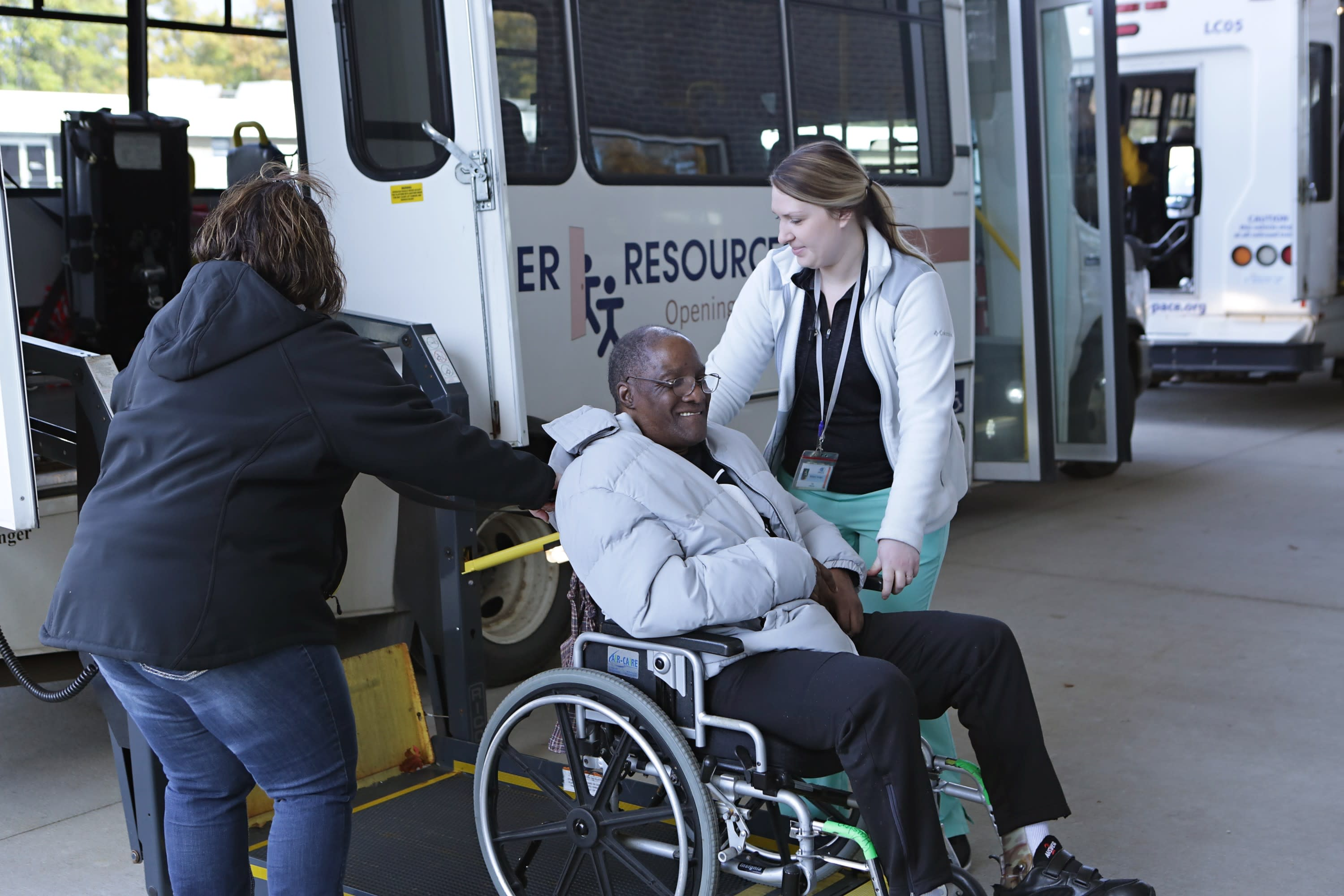 A senior gentleman who is in a wheelchair gets assistance to ride a LifeCircles PACE bus.