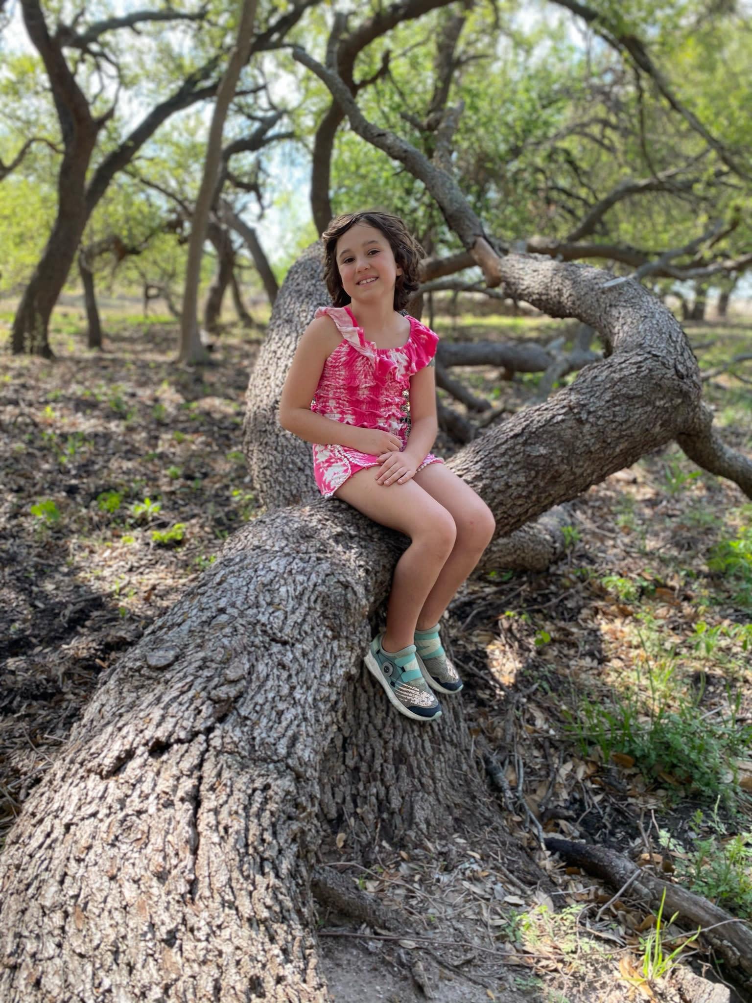 girl sitting on tree trunk