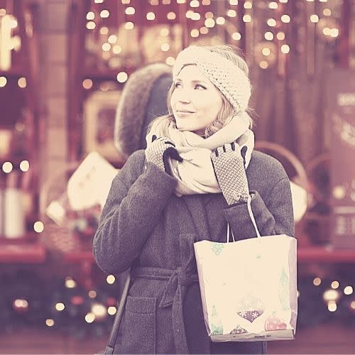 Woman shopping in winter coat with holiday lights in background