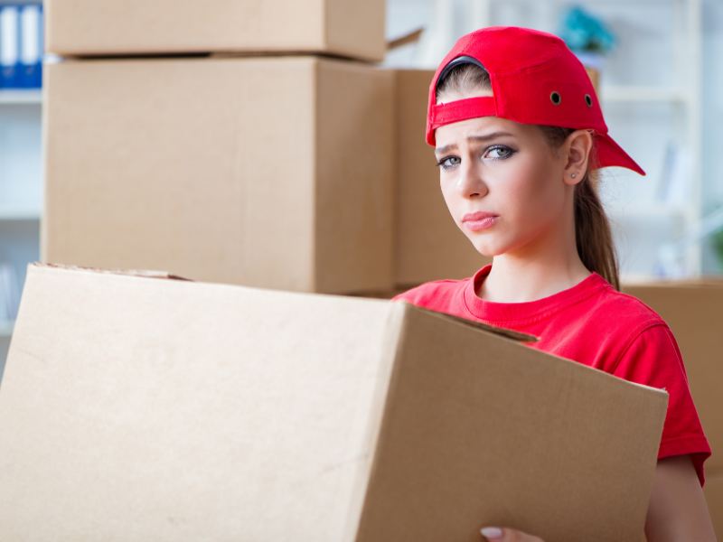 """Young woman carrying boxes, symbolizing """"Do You Know What You're Buying?"""""""