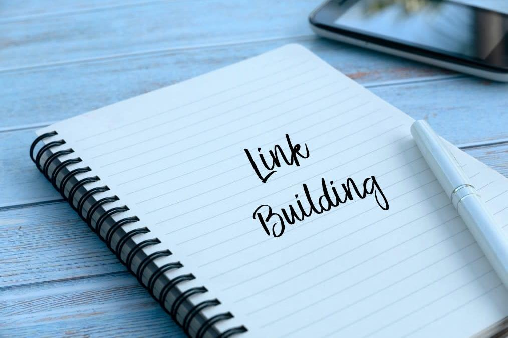 """notebook on a table with the words """"Link Building"""" on top"""