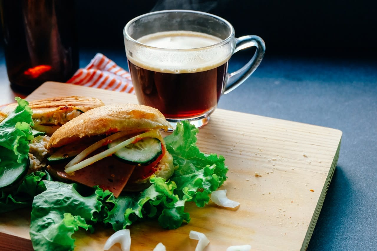 Photo of a sandwhich and a cup of tea or coffee