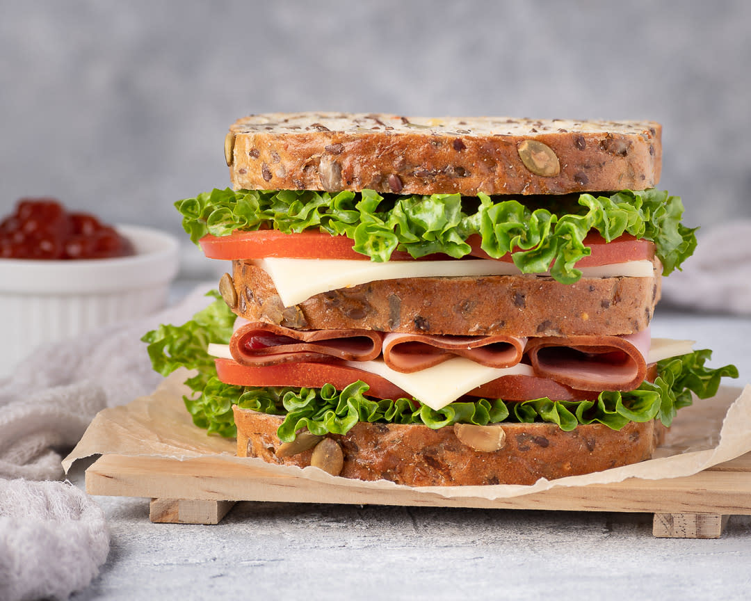 Food photography of a ham sandwich with whole grain bread, lettuce, tomato, cheese and ketchup