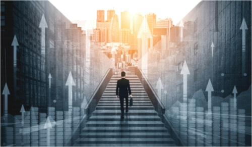 Business man climbing steps leading to sunlit center of city