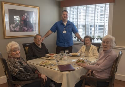 Image of a staff member and four residents at One MacDonough Place.
