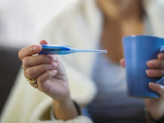 Woman with flu holds thermometer and mug of tea.