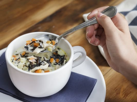 Cup of hearty cream of chicken and wild rice chowder.
