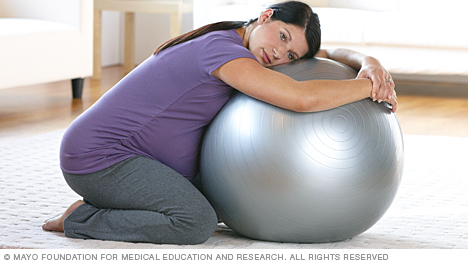 Woman in labor kneeling on birthing ball