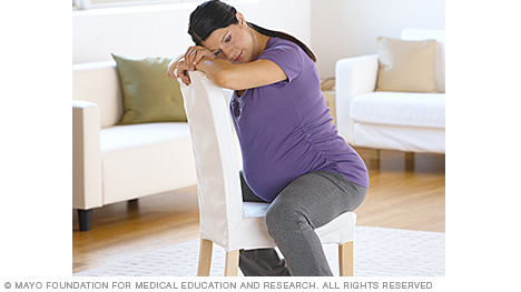 Woman in labor leaning forward against a chair