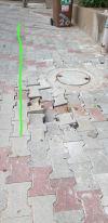 אבנים משתלבות שקרסו עקב סחף החול לבריכת הביוב השבורה