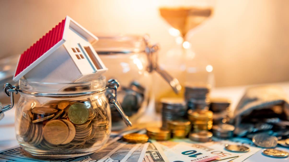 אילוסטרציה ללקיחת משכנתא: בית בתוך צנצנת כסף