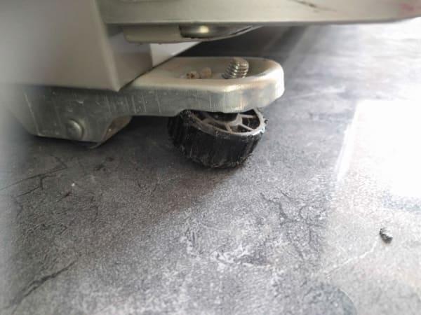 רגל הייצוב של המקרר שהתעקמה ודוחקת את המקרר למעלה בפינה.