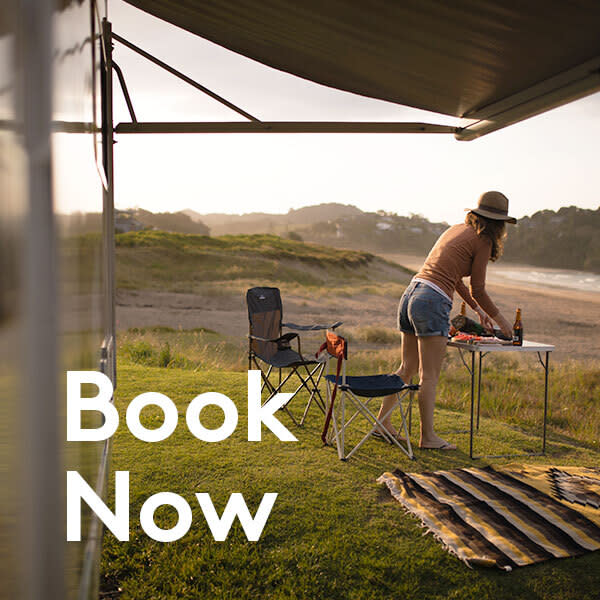 Book now text over image of woman camping outside motorhome
