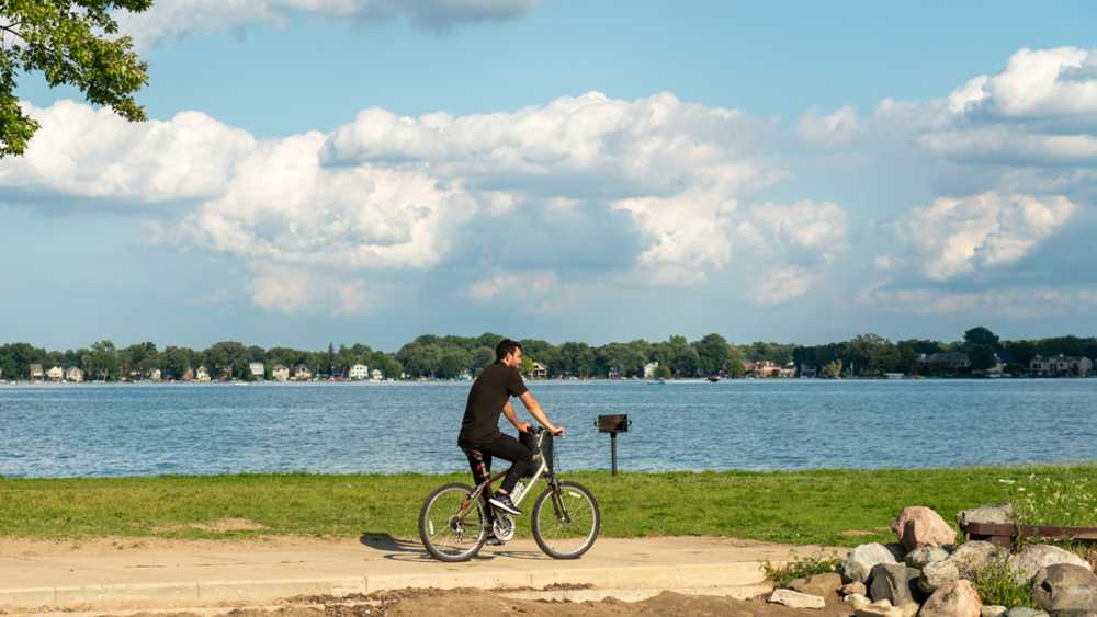 A man riding a bicycle on a path near the lake