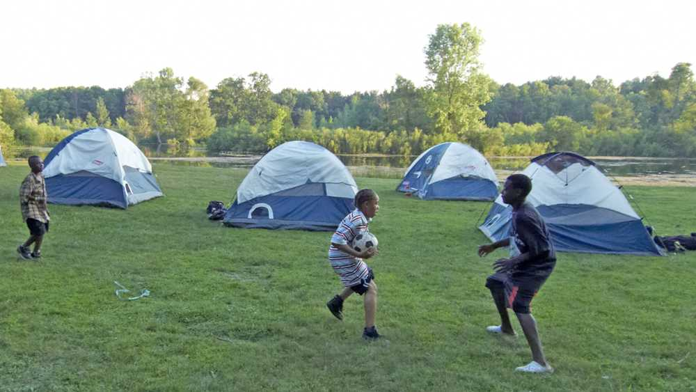 Boys playing in the grass near a group of tents