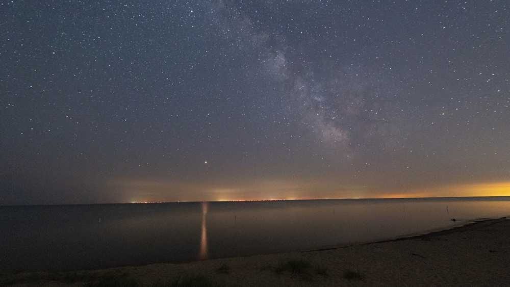 Stars twinkle in the dark sky above Tawas Bay on a summer night.