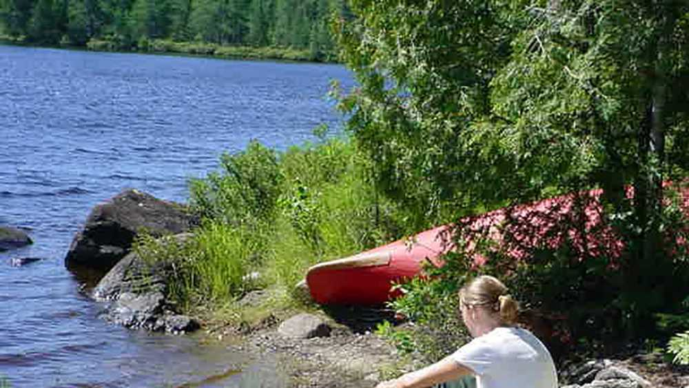 A woman sits near a canoe on the rocky shore of Craig Lake.