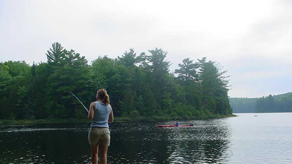 A woman is fishing in Craig Lake as she  stands on a rock near a canoe.